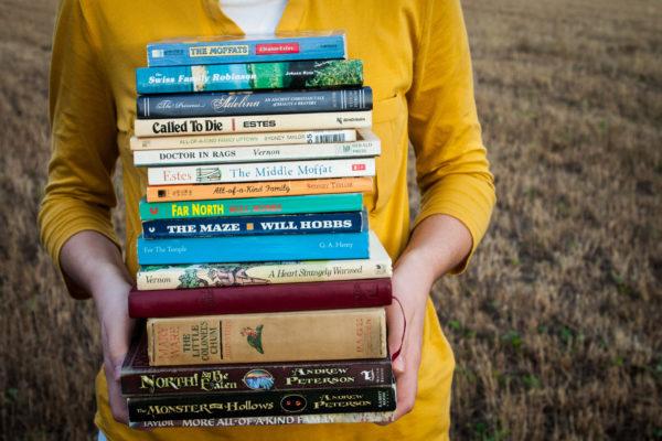 Ilustračný obrázok: žena drží kopu kníh